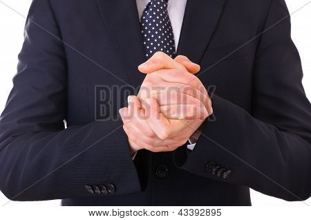 Business man rubbing his hands together.