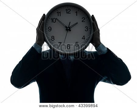 one caucasian businessman holding clock in silhouette studio isolated on white background
