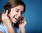 attractive teen girl listening to music on headphones and winking, portrait over blue background wit