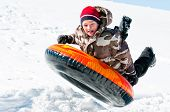 stock photo of sled  - A happy boy up in the air on a tube sleding in the snow.