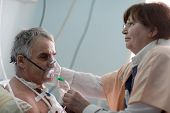 stock photo of oxygen  - Doctor is setting oxygen mask on a patient - JPG