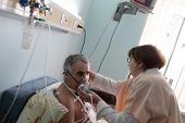 picture of oxygen mask  - Nurse is setting oxygen mask on patient - JPG