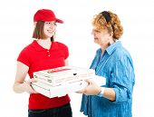 Woman receiving delivery of fresh hot pizza from a teenage delivery girl.  Isolated on white.