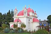 White walls, pink domes and golden crosses the Orthodox Church of the Twelve Apostles. The shore of
