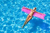stock photo of mattress  - sexy girl floating on a mattress in the sea or swimming pool - JPG