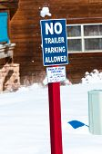 picture of allowance  - A blue no trailer parking allowed sign on a red wood pole in the snow - JPG