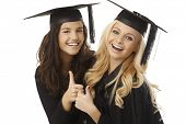 stock photo of convocation  - Beautiful young female graduates in square academic cap showing ok sign - JPG