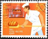 A stamp printed in Switzerland shows baker working
