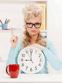 picture of attractive businesswoman with clock and finger up