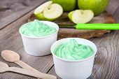 stock photo of gelato  - Serving of frozen homemade creamy ice yoghurt with fresh green apples and wooden spoon - JPG