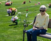 stock photo of broken heart flower  - An elderly woman sitting alone on a cemetery bench grieving - JPG