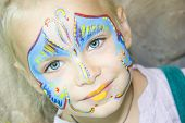 image of school carnival  - Beautiful girl with blue eyes with painted butterfly on her face - JPG