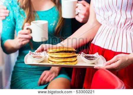 Friends or couple eating fast food for breakfast with pancakes and coffee in American fast food diner, the waitress serving the food