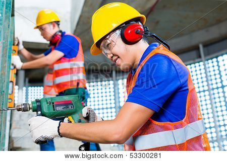 Asian Indonesian construction site workers  drilling with a machine or drill, bubble level, ear protection, gloves and hardhat or helmet in a wall of a tower building