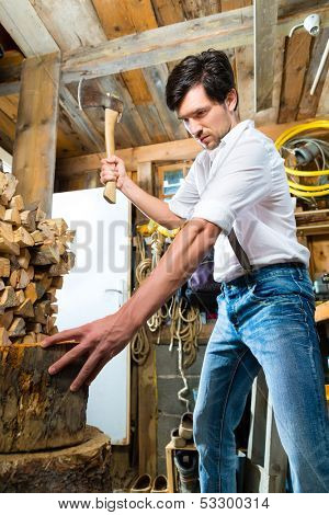 Young man chops firewood or wood with a hatchet or an axe in a shack in the mountains