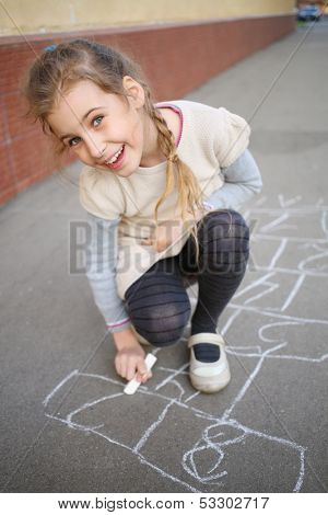 A smiling girl with a pigtail ends draw hopscotch on the pavement