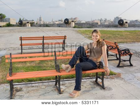 Girl Relaxing In A Orange Coloured Bench