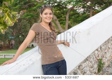 Girl Relaxing In A White Painted Stone Fence