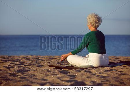 Elder Woman Doing Yoga Meditation On Beach