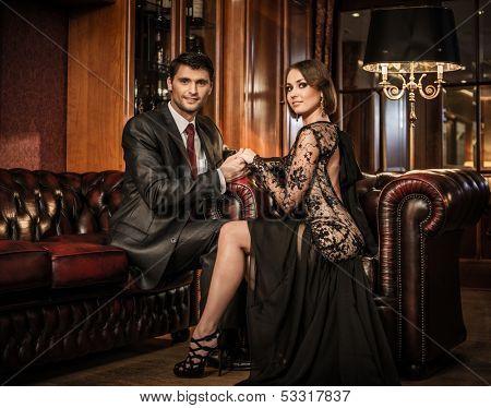 Elegant well-dressed couple in luxury interior