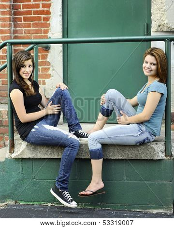 Two young teen girls relaxing together on an old warehouse stoop.