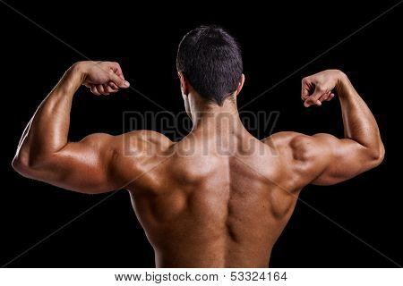 Muscle young man showing his back muscles against a dark background
