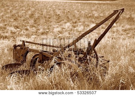 Antique Plow Abandoned in a Field in Sepia
