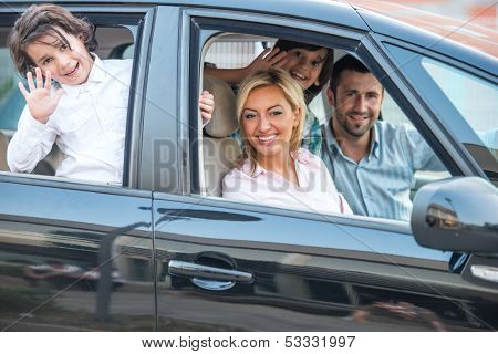 Happy smiling family posing in car