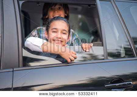 Cute smiling kids looking through car window from backseat