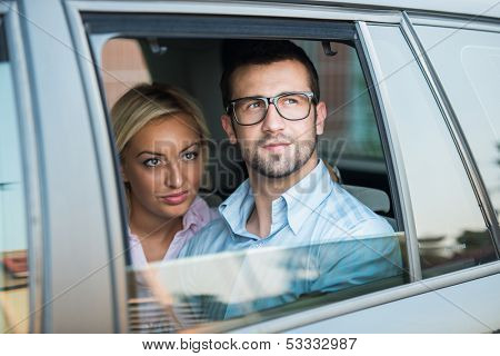 Handsome young couple looking from a car backseat