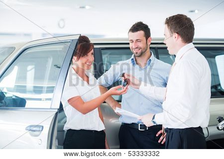 Couple getting car keys from a car seller