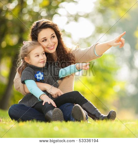 Happy woman and daughter showing to something in the park