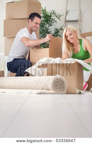 Merry young couple unpacking boxes in their new house