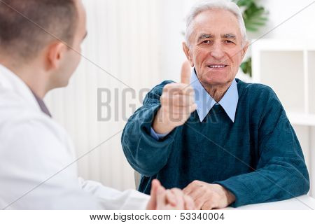 satisfied senior patient at doctor showing thumbs up,