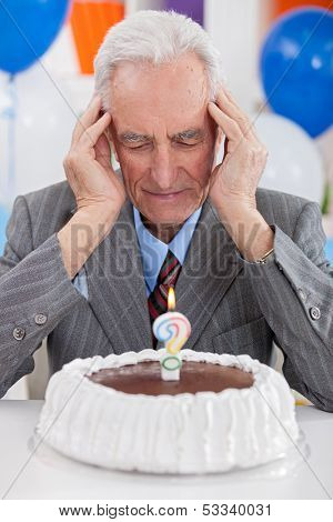 Senior man looking at  birthday cake thoughts about his age