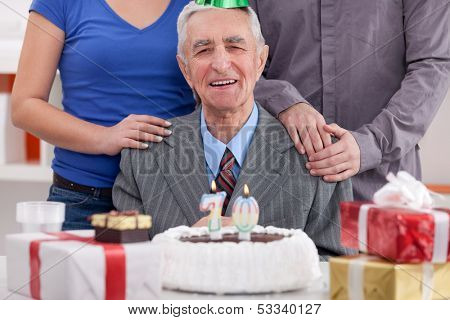 Happy senior man celebrating his 70th birthday with family