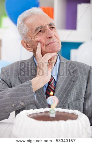 senior man with birthday cake thinking how old is