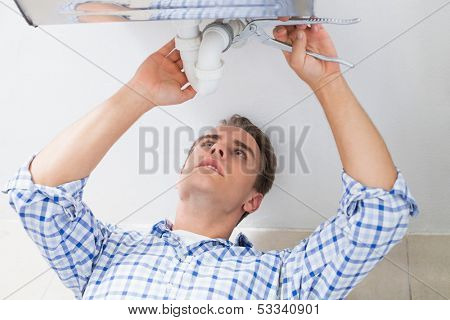 Close up of a young plumber repairing washbasin drain in bathroom