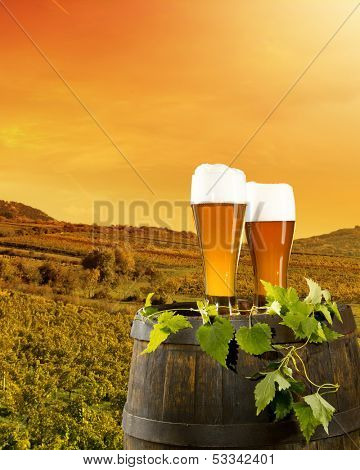 Beer keg with glasses of beer on rural countryside background