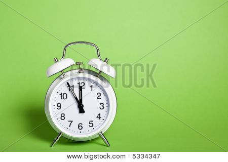 Classic Alarm Clock On Green Background