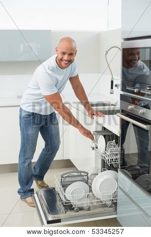 Portrait of a smiling young man using dish washer in the kitchen at home