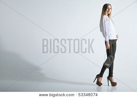 Fashionable woman with a bag in light background