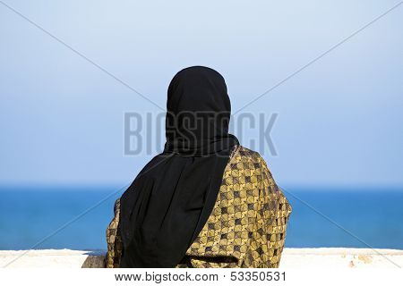 Arab woman with Islamic headscarf looking over the ocean