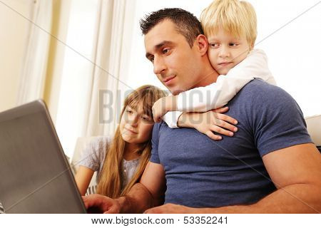 Father with children working on laptop computer at home