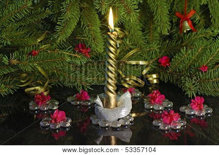 golden burn candle under  Christmas tree