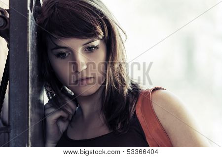 Sad young woman at the wall