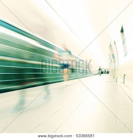 Train in motion blur and blurred people at subway station.