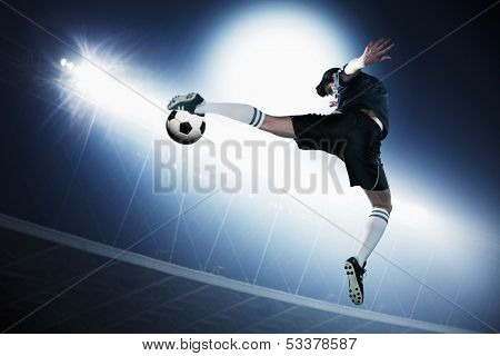 Soccer player in mid air kicking soccer ball