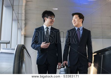 Two smiling businessmen coming up the escalator together