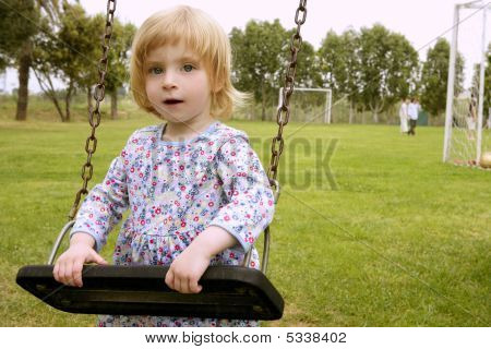 Beautiful Toddler Blond Girl Playing On The Park